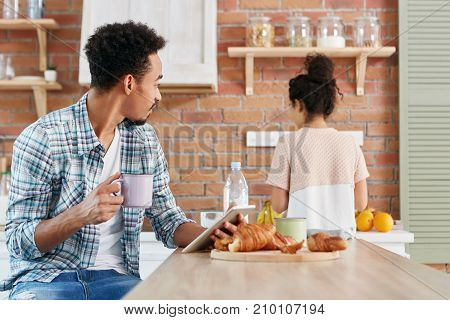 Family Relationship, Routine Concept. Mixed Race Dark Skinned Afro American Male Uses Tablet For Com