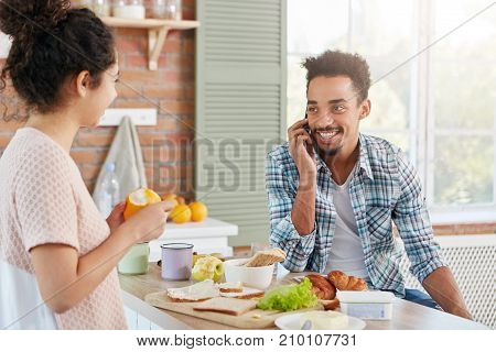 Portrait Of Dark Skinned Man Has Beard And Mustache Calls His Friend As Wants To Invite Him For Lunc
