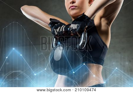 fitness, sport, exercising, weightlifting and people concept - young woman flexing muscles with kettlebell in gym