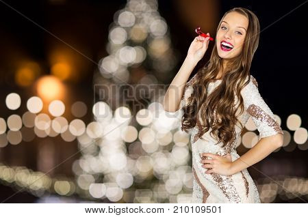 holidays, celebration and people concept - happy young woman or teen girl in fancy dress with sequins and party blower over christmas tree lights background
