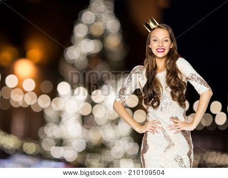 people, holidays and celebration concept - happy young woman or teen girl in party dress and princess crown over christmas tree lights background