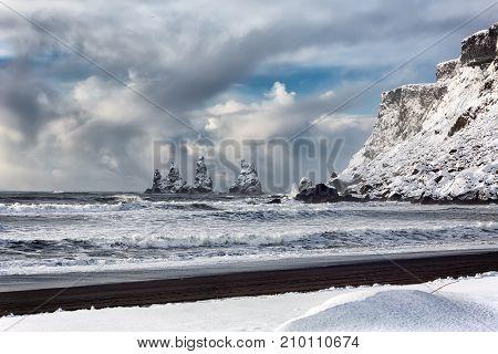 Basalt rock formations Troll toes on black beach in winter. Reynisdrangar, Vik, Iceland