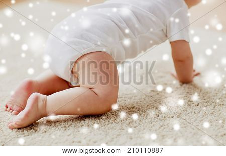 childhood, babyhood and people concept - little baby boy or girl crawling on floor over snow