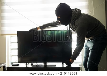 House Robber Taking A Tv With Him