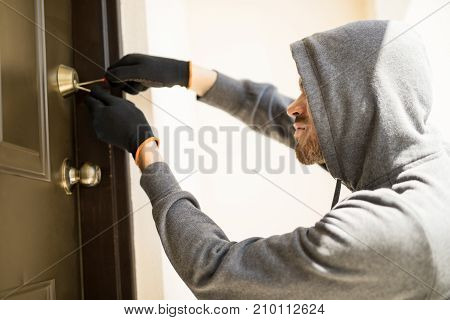 Burglar Picking Lock Of A House