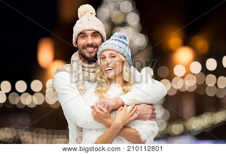 christmas, holidays and people concept - happy couple in hats and scarf hugging over night lights background