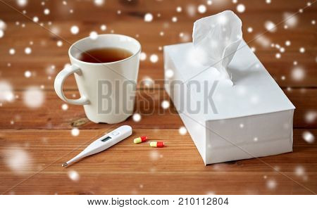 healthcare, medicine, flu and treatment concept - cup of tea, paper wipes and thermometer with pills over snow