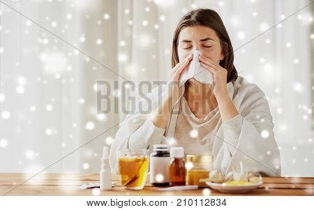 health care, flu, hygiene, age and people concept - sick woman with medicine blowing nose to paper wipe at home over snow