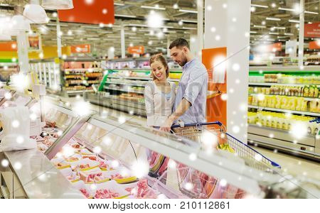 food, sale, consumerism and people concept - happy couple with shopping cart buying meat at grocery store or supermarket over snow