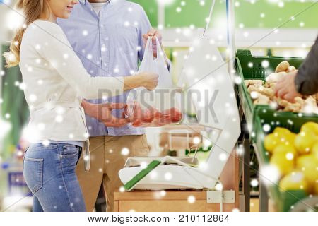 shopping, food, sale, consumerism and people concept - happy couple weighing tomatoes on scale at grocery store or supermarket over snow