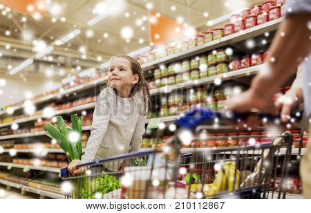 family, sale, consumerism and people concept - happy child and father carrying shopping cart buying food at grocery store or supermarket over snow