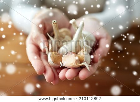 health, people, food, traditional medicine and ethnoscience concept - woman hands holding garlic for cooking or healing over snow