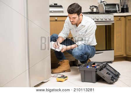 Male Technician Writing A Work Report