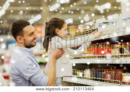 family, sale, shopping, consumerism and people concept - happy father with child buying food at grocery store or supermarket over snow