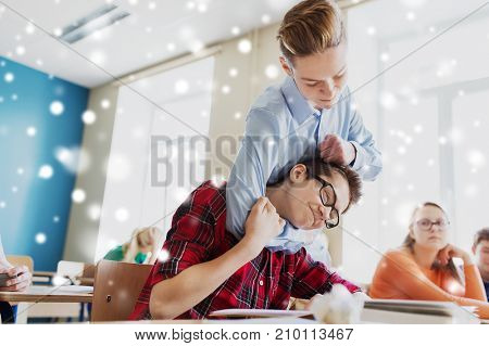 education, bullying, violence, aggression and people concept - student boy suffering of classmate mockery over snow