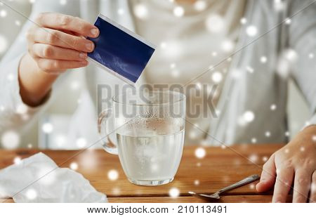 healthcare, medicine and people concept - close up of ill woman pouring medication powder into class mug with spoon over snow