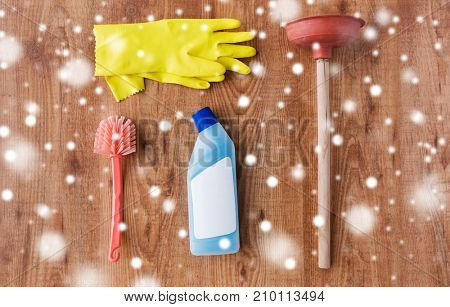 cleaning stuff, housework, housekeeping and household concept - plunger, rubber gloves and toilet brush with detergent on wooden background over snow