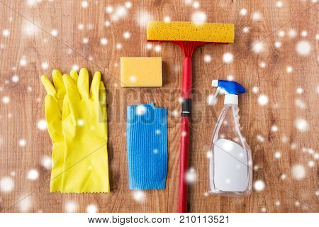 housework, housekeeping and household concept - squeegee with rubber gloves and window cleaning stuff on wooden background over snow