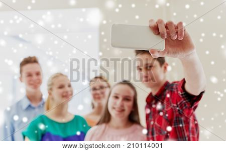 education, school, technology and people concept - group of happy smiling students taking selfie with smartphone in corridor over snow