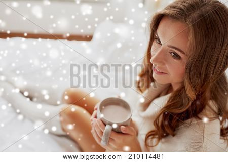 christmas, winter and people concept - happy young woman with cup of coffee or cocoa in bed at home over snow