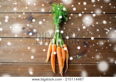 healthy eating, food, diet and vegetarian concept - carrot bunch on wooden table over snow