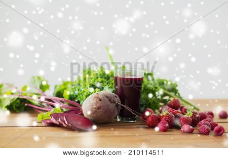 healthy eating, food, diet and vegetarian concept - glass of beetroot juice, fruits and vegetables on wooden table over snow