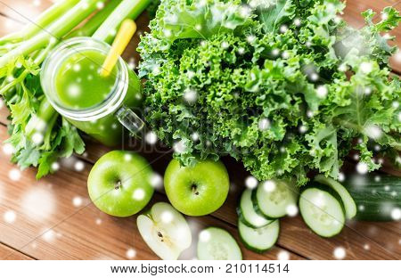 healthy eating, food, diet and vegetarian concept - close up of glass jug with green juice, fruits and vegetables on wooden table over snow