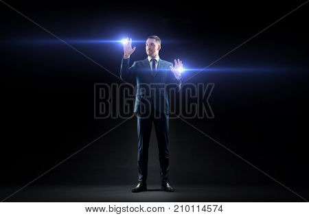 business, people and future technology concept - businessman in suit with laser lights over black background