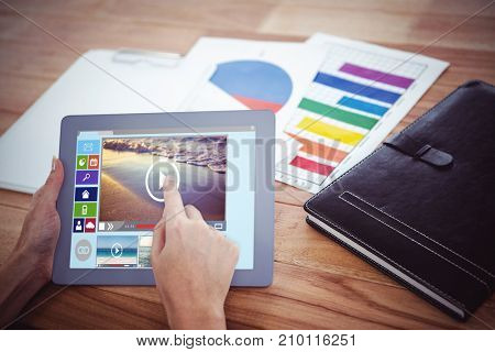 Composite image of various video and computer icons against over shoulder view of hipster woman using tablet