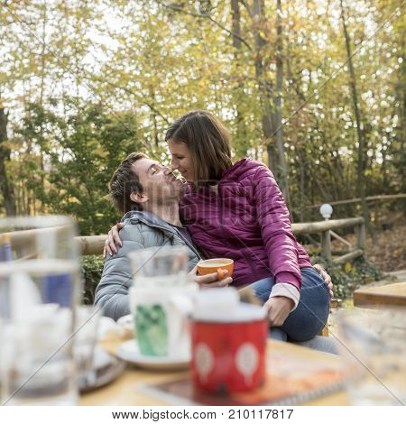 Romantic man and woman sitting on an outdoor patio in an autumn garden in a loving embrace about to seal a kiss viewed over a table of food and drinks.