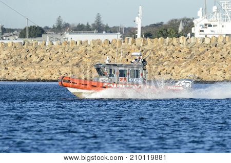 Fairhaven Massachusetts USA - October 20 2017: Fairhaven Fire Department 25-foot patrol boat throwing up spray with hurricane barrier in background