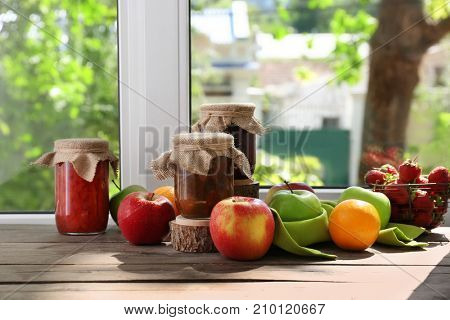 Jars with jam and fruits on windowsill