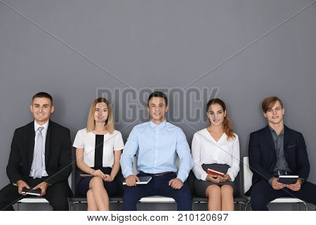 Group of people waiting for job interview on gray wall background