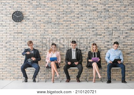 Group of people waiting for job interview on chairs