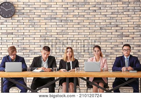 Group of people waiting for job interview at table