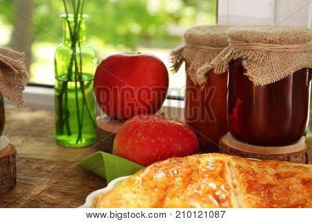 Glass jars with jam and delicious pie on windowsill