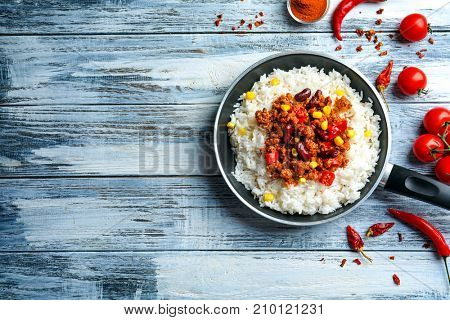 Frying pan with chili con carne and rice on wooden background