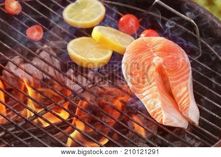 Salmon steak with lemon on barbecue grill, close up
