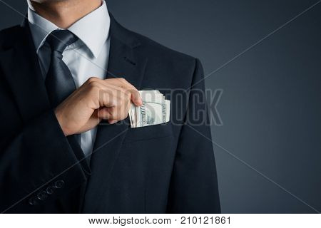 Man with money in pocket on dark background