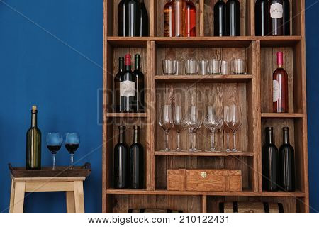 Wooden storage stand with wine bottles and glasses indoors
