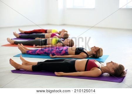 Group of young women practicing Shavasana pose in yoga class