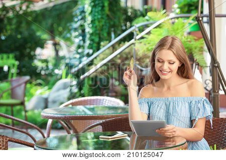 Young woman with tablet and credit card in cafe