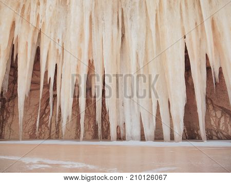 Strange and mysterious giant icicles resembling a pipe organ or stalactites hang from the arch of a sandstone cave and hit an icy surface of a frozen lake. A flooded sand quarry in winter.
