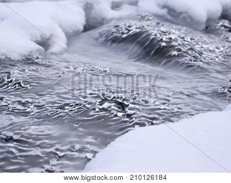 The ice on a surface of a frozen winter brook forms ripples waves and whirlpools. The riversides are covered with snow.