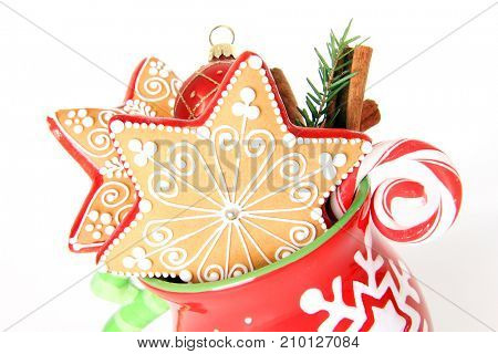 Professionally decorated Christmas cookies in a holiday mug with a candy cane and holiday bauble.