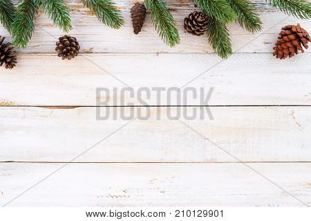 Christmas background - fir leaves and pine cones decorating elements rustic on white wood table. Creative Flat layout and top view composition with border and copy space design.