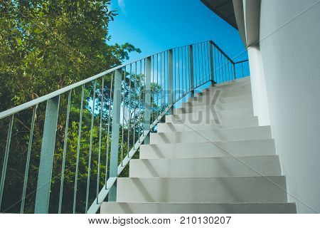 Front view close up of empty white concrete staircase and metal railing at outside buildings with blue sky background in vintage style.