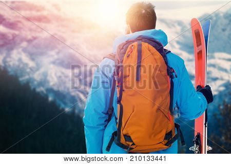 Rear view of skier with backpack holding skis against scenic view of forest and snowy mountain range