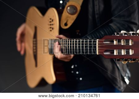Close up photo of young musician holding acoustic guitar, focus is on neck