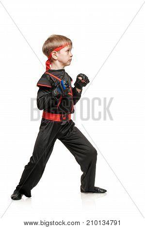 Little boy in kimono doing martial arts exercises. Cosplay hero ninja